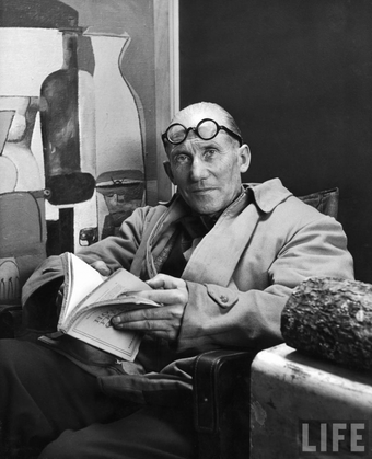 Architect Le Corbusier sitting in chair & holding book in hands-- Paris France 1965.