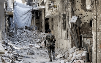 A Syrian rebel fighter walks down a street in Damascus that has been reduced to rubble.