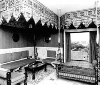 Interior of a guest room. Both the guest rooms and restaurants have brightly panelled walls and wood furnishings from Rajasthan and ocher regions. Some rooms include an Indian low sitting and resting platform (taq) in the bay window.