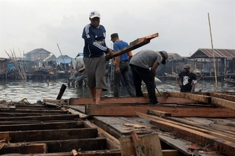 Workers dismantle the wooden deck of a collapsed three-storey floating school, resting on top of 250 empty plastic b