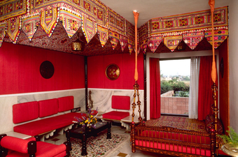 Interior of a guest room. Both the guest rooms and restaurants have brightly panelled walls and wood furnishings from Rajasthan and ocher regions