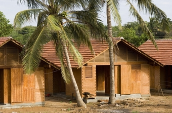 Each of the 100 homes has walls made with earth bricks, while partitions and finishings are comprised of local rubber tree wood. A shared entertainment space is covered, allowing for community activities.