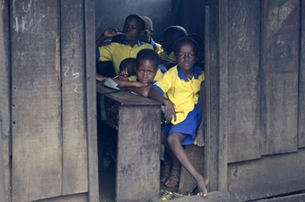 Students of the Whanyinna floating school look on at the main site of the school, near to a collapsed three-storey annex, on June 9, 2016 in Lagos.