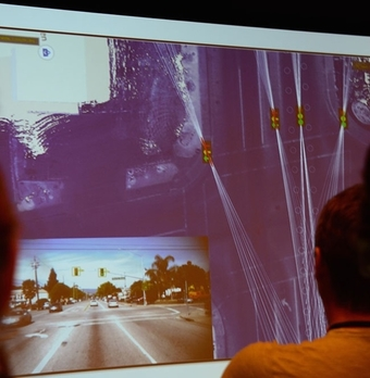 """A Google employee demonstrates what the self-driving car """"sees."""" Note the background world on which the light traffic lights and their sightlines are displayed: that's the track."""