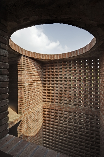 The prayer hall separates itself from the rest of the structure by open-to-sky light wells between the cylinder and the inner square. Light pours down on the unplastered brick walls, giving it a primordial character