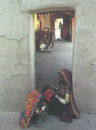 The vistāra through a Banni doorway. Woman sewing in foreground typifies the area's strong crafts tradition, especially noted for its fine and delicate embroidery.
