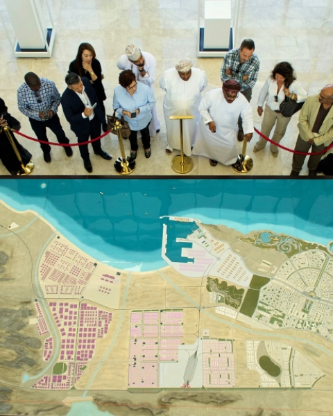 Potential investors examine a map of future plans for Duqm