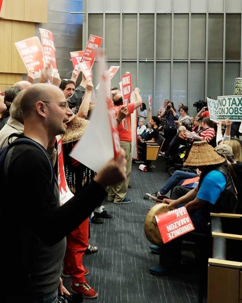 Supporters at left of a tax on large companies face off against opponents of the tax at City Hall in Seattle, June 12, 2018.