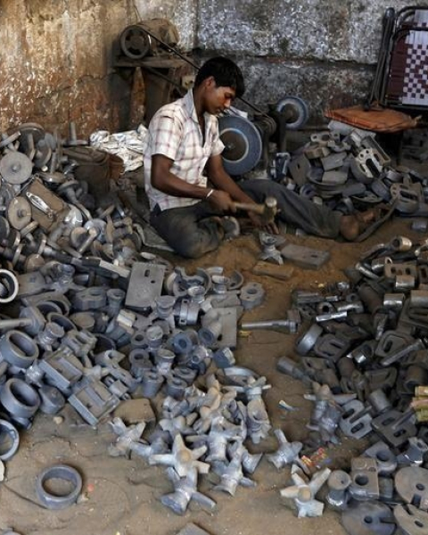 A worker separates casting joints of gearboxes inside a small-scale automobile manufacturing unit in Ahmedabad, India, October 12, 2015.