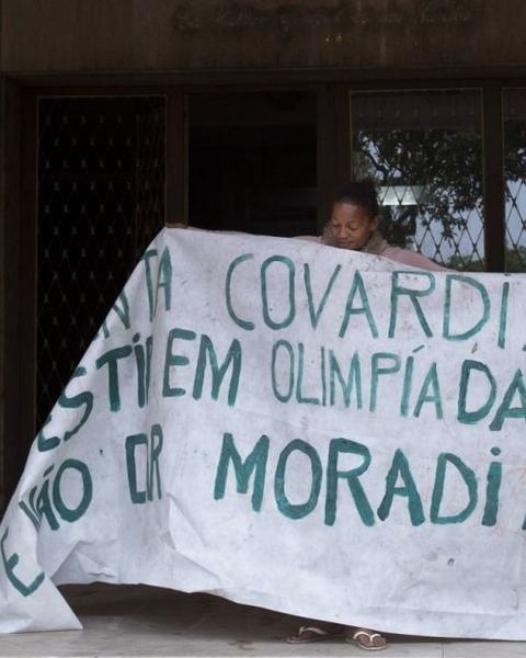 "A woman holds a banner that reads (translated from Portuguese) ""Such cowardice. Investment in Olympics and not housing."""