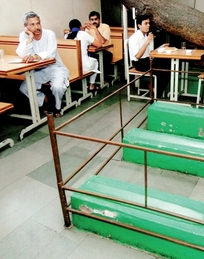 Customers wait for their orders next to graves inside Lucky Cafe in Ahmedabad