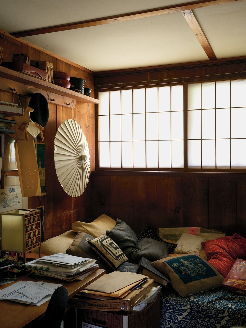 In a guest bedroom, a Japanese umbrella shade hangs over a bed piled with cushions