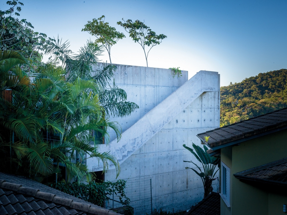 In the beach town of Ubatuba, Brazil, rises a reinforced concrete house — with an external staircase in the same material — built in 2014 into the canopy by the São Paulo architect Angelo Bucci and his firm SPBR
