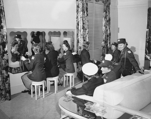 American servicewomen chat and apply makeup in the powder room of a women's military-services club in New York during World War II.