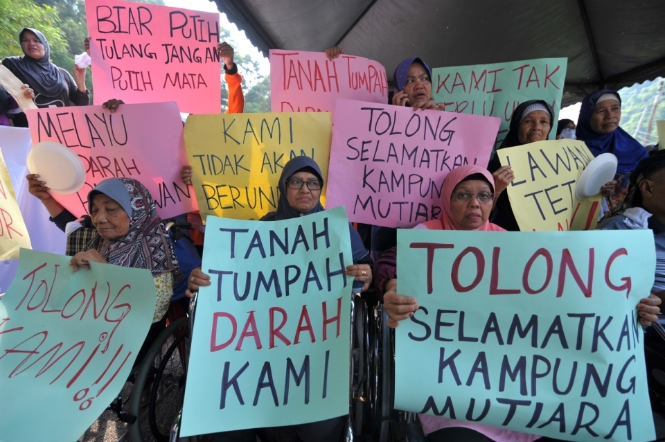 Residents holding placards during the protest at Kampung Mutiara today.