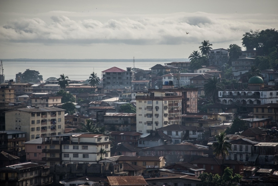 A view of central Freetown. A handful of board houses are scattered among the concrete ones.
