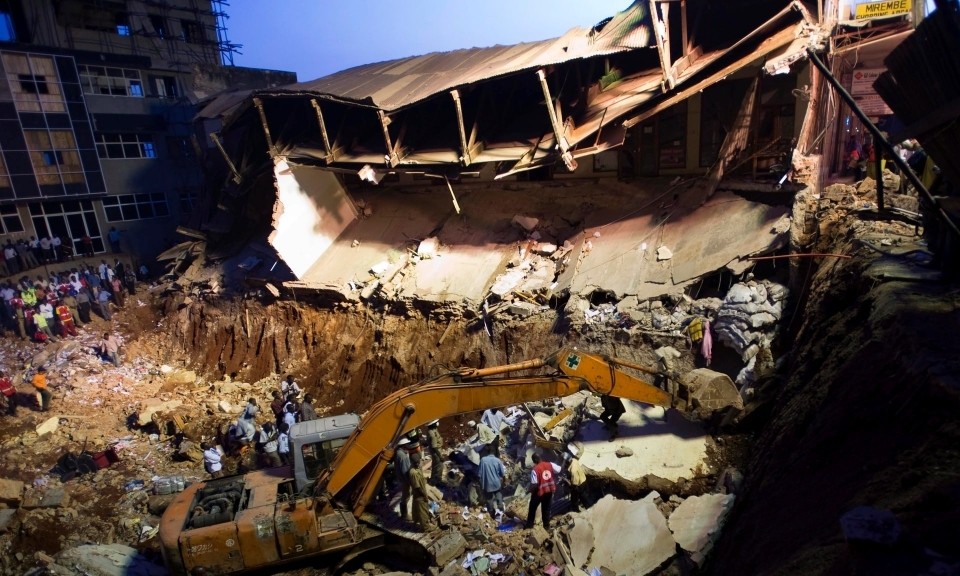 Rescue workers and onlookers at the scene of a building that collapsed in Kampala in 2009.