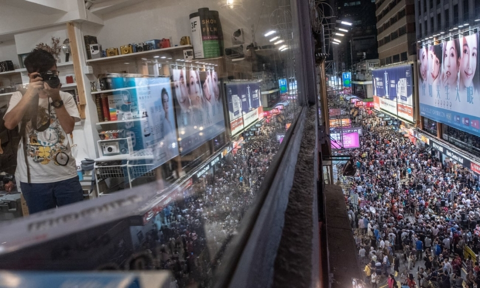 A man takes photographs in a shop above the chaotic pedestrian zone of Sai Yeung Choi Street South on the last day before vehicles returned