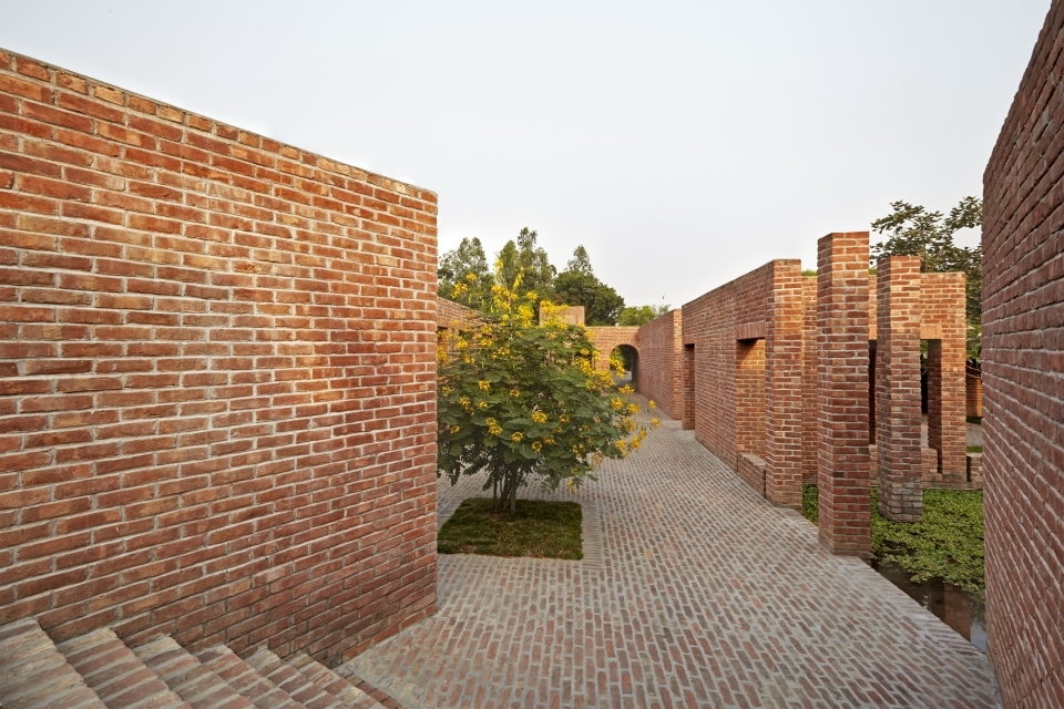 The access to the building from the earthen bundh is organised via two entrance stairs at opposite ends. The programme is then organised around a series of pavilions, courtyards and reflecting pools