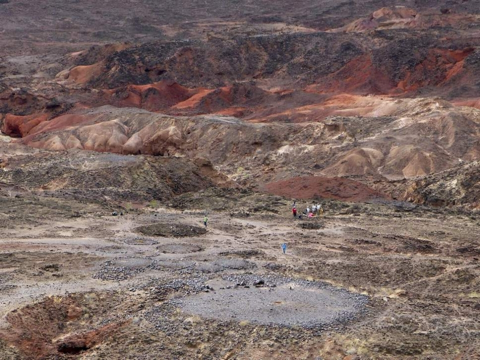 View from the high volcanic ridge overlooking Lothagam North Pillar site. In the foreground, the 30m platform contains the mortuary cavity, and is ringed by boulders, with a linear arrangement of pillars on its east side ( PNAS )