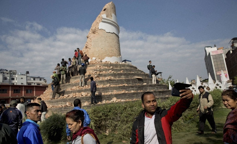 A man takes a selfie at the historic Dharahara Tower, a city landmark, that was damaged in Saturday's earthquake in Kathmandu, Nepal, Monday, April 27, 2015.