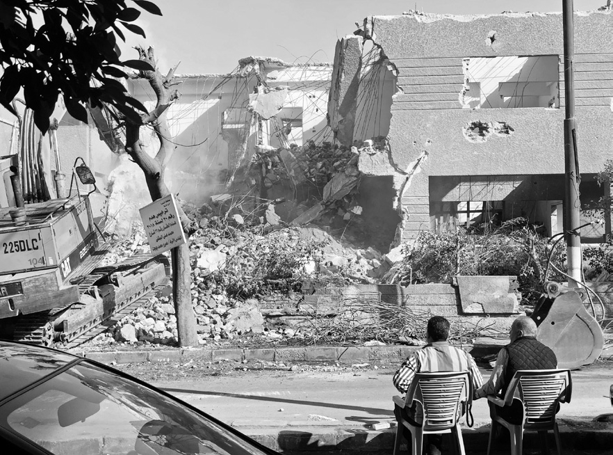 Two men watch as a two-story Modernist house is demolished in Heliopolis in November 2018