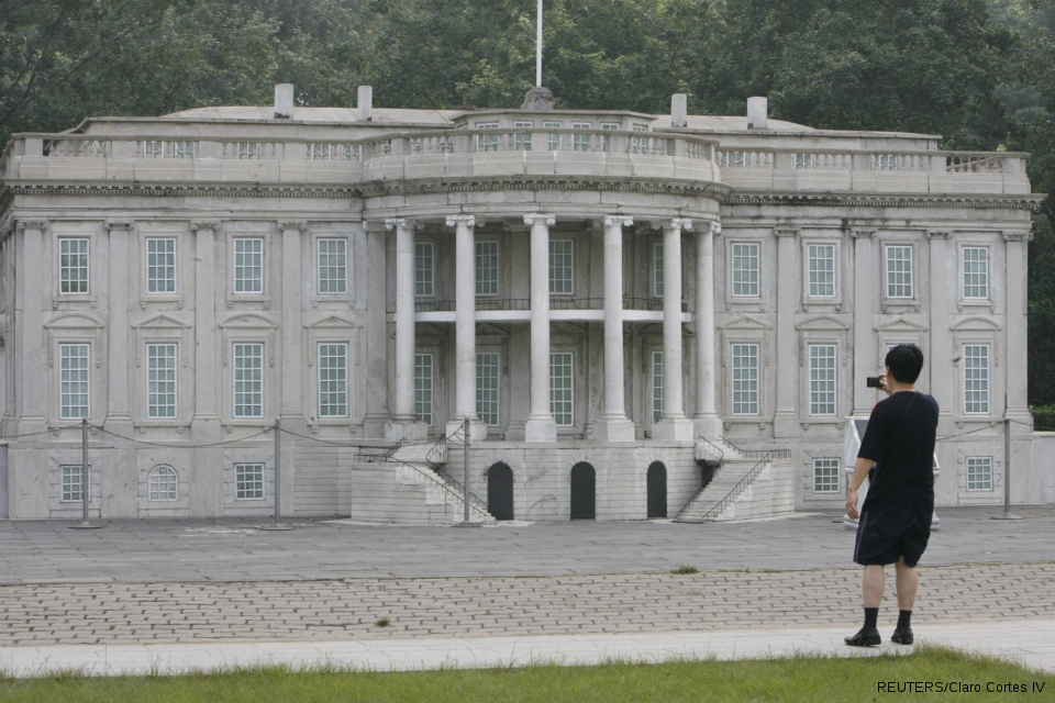 """A visitor takes photographs of a replica of the White House at Beijing World Park, one of the three designated """"protest parks"""" in Beijing, on July 25, 2008."""