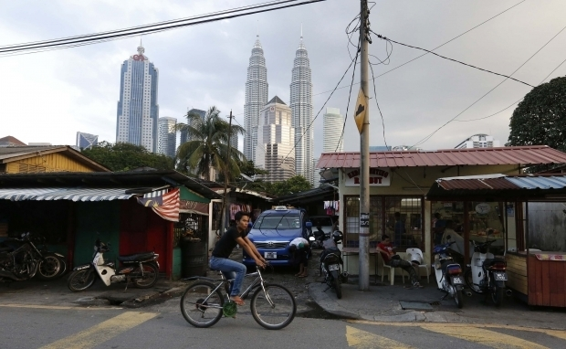 A cyclist passes small businesses in Kampung Baru.