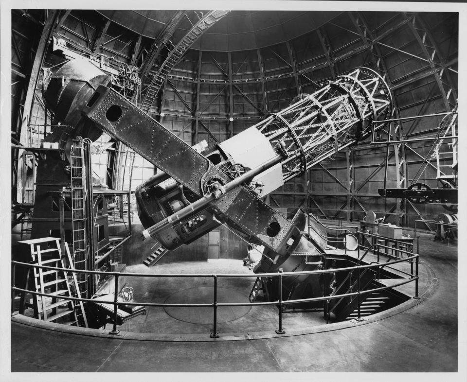 The Hooker 100-inch reflecting telescope, side view with tube 40 degrees from horizontal. Edwin Hubble's chair, on an elevating platform, is visible at left