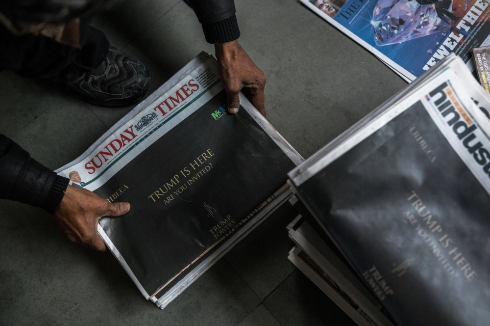 A vendor stacking newspapers with advertisements for the proposed Trump towers development in Gurgaon.