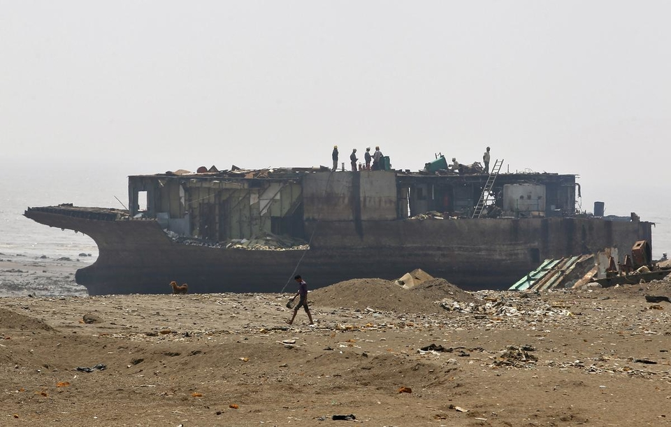 Workers dismantle a decommissioned ship at the Alang shipyard in Gujarat, March 27, 2015.