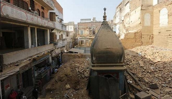Razed down: Rubble from demolished buildings cover a temple in Varanasi. Demolition work is being carried out for the Kashi Vishwanath Temple Corridor