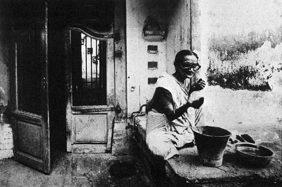 A woman performs her household chores outdoors. From the pol's main street, a number of cul-de-sacs lead off and most residents regard these lanes as extensions of their houses.