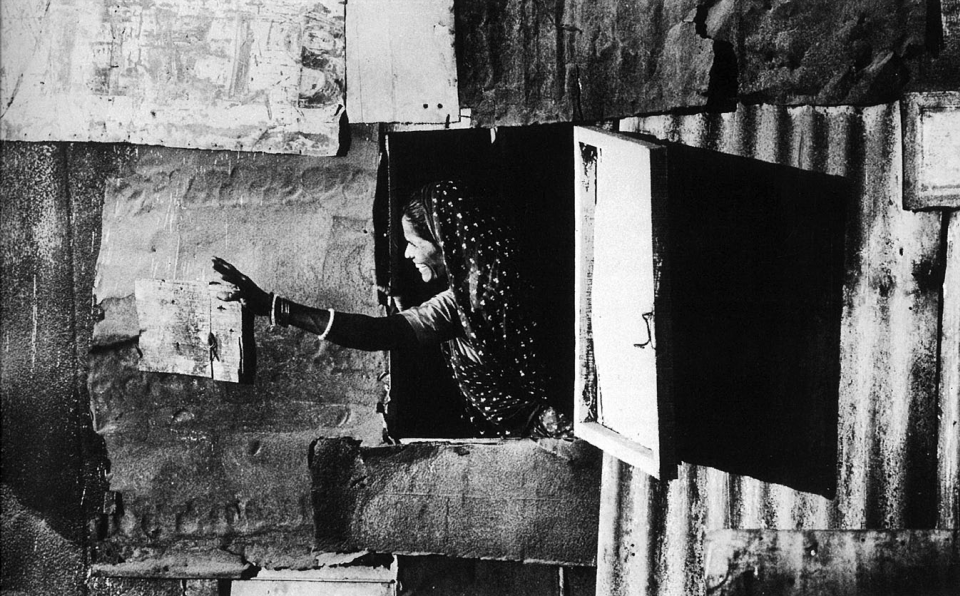 Woman waves happily from her hutment of corrugated iron – favourite building material of squatters.