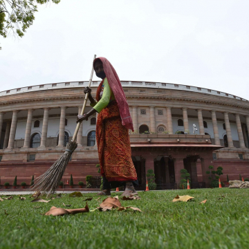 A worker cleans the lawn at Parliament House