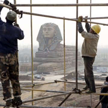 Laborers work on scaffolding near a full-scale replica of the Sphinx at an unfinished movie and animation tourism theme park in Chuzhou, Anhui province, on March 27, 2015.